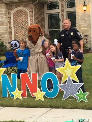 Prosper Police Officer and McGruff the Crime Dog pose with some neighborhood kids during National Night Out on Tuesday October 3